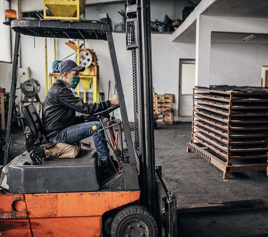 Man riding forklift in coal in factory